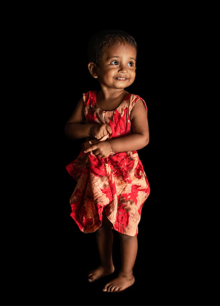 Baby girl Ayedatujannah at 1 year old. She wears in a red floral pattern one-piece dress and stands on her own. She looks to her left-hand side with a radient smile. Photo credit: © UNICEF/UN0336462/Babajanyan VII Photo