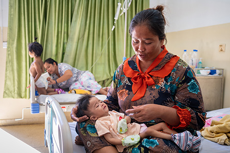 Baby Plearith is on his mother's lap in a ward at National Pediatric Hospital in Cambodia